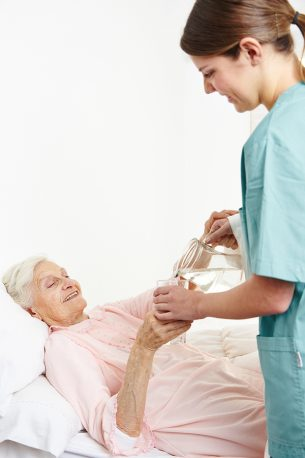 bigstock-Geriatric-nurse-giving-water-t-55192541-e1538161885773.jpg